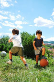Two little kids with basketball and football — Stockfoto