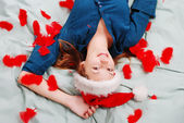 Adorable girl with santa hat laying on bed — Stock Photo