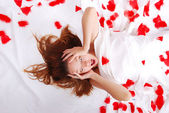 Beautiful girl laying on bed with white sheets screaming — Stock Photo