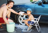 Child washing car and toy car with his father — Stock Photo