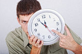 Young male model with clock in front of his head — Stock Photo