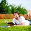 Young attractive man on green meadow — Stock Photo