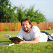 Young attractive man on green meadow with a book — Stock Photo