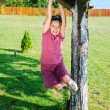 Little cute girl is playing on tree — Stock Photo