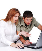 Two young models on laptop with surprised faces — Foto de Stock