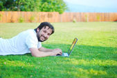 Happy young man working on laptop in beautiful green enviroment — Stock Photo