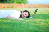 Young attractive man on green meadow with laptop — Stock Photo