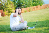 Happy young man on green meadow with laptop — Stock Photo