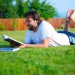 Young man is laying on green ground and learning — Stock Photo