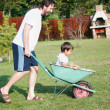 Father is playing with kid driving him on green meadow — Stock Photo #21460065