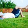 Stock Photo: Young man is laying on green ground and sleeping