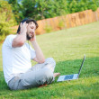 Young man is sitting on green ground and taking a nice time — Stock Photo