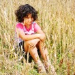 A little pretty girl siting on wheat field — Stock Photo