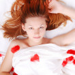 Stock Photo: Beautiful girl in bed with red plumage