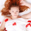 Beautiful girl in bed with red plumage — Stock Photo