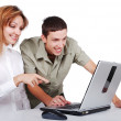 Two young on the desk are smiling and poiting at the laptop — Stock Photo