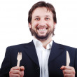 A young male holding fork and spoon in hands — Stockfoto