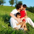 Young father in white with children on beautiful meadow — Stock Photo