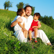 Young father in white with children on beautiful meadow — Stock Photo #21464879