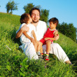 Stock Photo: Young father in white with children on beautiful meadow
