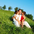 Young father in white with children on beautiful meadow — Stock Photo #21464913