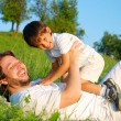 Young father in white with child on beautiful meadow — Stock Photo #21464963