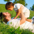 Young father in white with child on beautiful meadow — Foto Stock