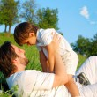 Young father in white with child on beautiful meadow — Stock Photo #21464987