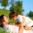 Young father in white with child on beautiful meadow — Stock Photo #21465031