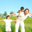 Young father in white with boys on beautiful meadow — Stock Photo