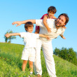 Young father in white with boys on beautiful meadow — Stock Photo #21465073