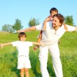 Stock Photo: Young father in white with boys on beautiful meadow