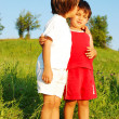 Two happy children hugging each other on meadow — Stock Photo #21465211