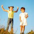 Happy little girl and kid jumping and joying in nature — Stock Photo