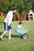 Father is playing with kid driving him on green meadow — Stock Photo