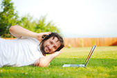 Young man is laying on green ground and taking a nice time — Stock Photo