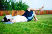 Young man is laying on green ground and sleeping — Stock Photo