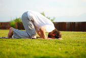 Muslim male is praying outdoor on green ground — Foto Stock