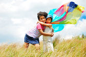 A little pretty girl and boy with scarf above head on medow — Stock Photo