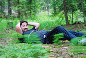 Young man relaxing in nature on ground — Stok fotoğraf