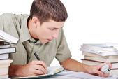 Junger mann am schreibtisch mit bücher schreiben — Stockfoto