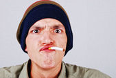 Funny face young man with cigarete in hand — Stock Photo