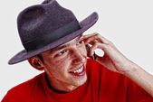 Young man with red shirt and black hat speaking on phone — Stock Photo