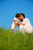 Young father in white with child on beautiful meadow — Stock Photo