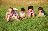 Happy little children in grass on meadow — Stock Photo