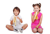 Two little children siting and eating banana — Stok fotoğraf