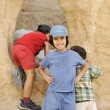 Stock Photo: Summer tourist vacation, children playing around the little cave