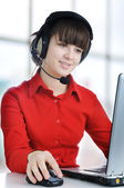 Beautiful customer support girl in front of laptop in an office — Stock Photo