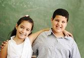 Two happy friends in front of green classroom board, school activities — Stock Photo