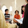 Foto Stock: Islamic education inside white mosque, teacher and children learning together (or mother and father with them)
